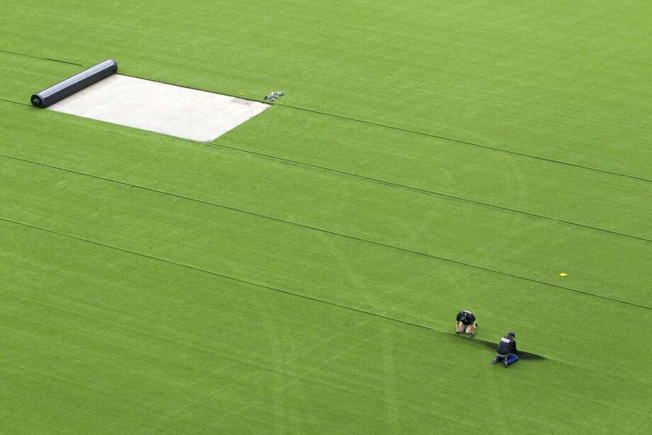 AstroTurf employees pull up the synthetic grass as it's removed from Reliant Stadium.  (Cody Duty / Houston Chronicle)