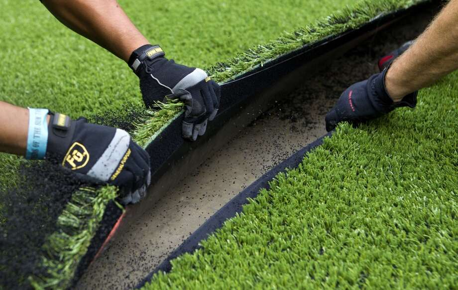 AstroTurf employees pull up the synthetic grass as it's removed from Reliant Stadium (Cody Duty / Houston Chronicle)