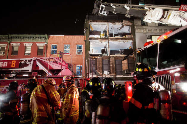 The facade of a four-story building on 14th Street and 8th Avenue collapsed onto the sidewalk as FDNY firefighters respond, Monday, Oct. 29, 2012, in New York. Hurricane Sandy bore down on the Eastern Seaboard's largest cities Monday, forcing the shutdown of mass transit, schools and financial markets, sending coastal residents fleeing, and threatening a dangerous mix of high winds, soaking rain and a surging wall of water up to 11 feet tall. (AP Photo/ John Minchillo) Photo: John Minchillo, Associated Press / FR170537 AP