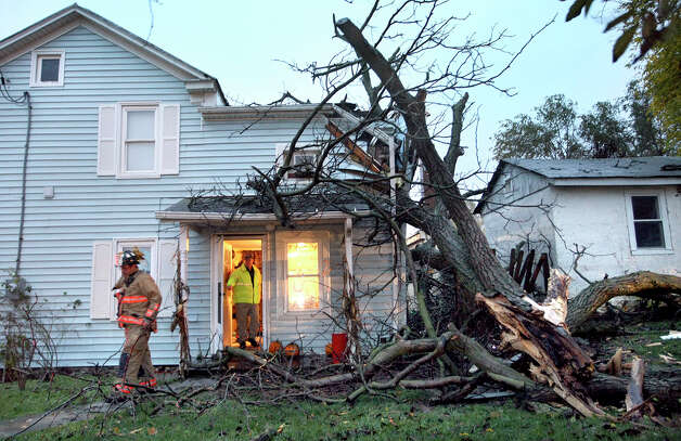 Winchester city firefighters leave a home after checking damage caused by a tree falling onto the back of the house on Monday evening Oct. 29, 2012 in Winchester, Va. Sandy continued on its path Monday, as the storm forced the shutdown of mass transit, schools and financial markets, sending coastal residents fleeing, and threatening a dangerous mix of high winds and soaking rain. Photo: Ginger Perry, AP / The Winchester Star