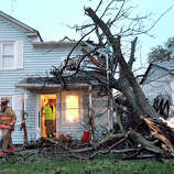 Winchester city firefighters leave a home after checking damage caused by a tree falling onto the back of the house on Monday evening Oct. 29, 2012 in Winchester, Va. Sandy continued on its path Monday, as the storm forced the shutdown of mass transit, schools and financial markets, sending coastal residents fleeing, and threatening a dangerous mix of high winds and soaking rain.