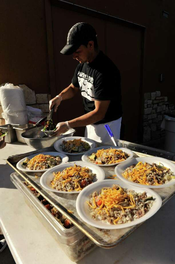 "Gabriel Corona of the Canyon Cafe prepares a Pedro Special for dogs attending the San Antonio Humane Society fundraiser, ""Paws on the Patio"" Monday afternoon. Photo: Robin Jerstad/For The Express-Ne"