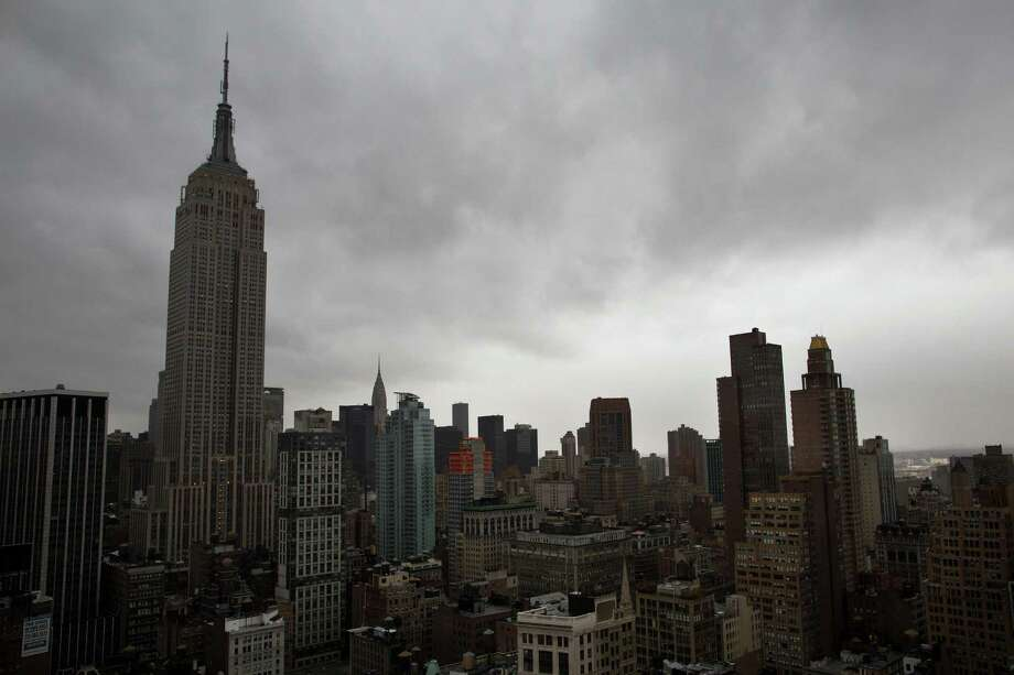 Storm clouds loom over the Empire State Building and Manhattan skyline, Monday, Oct. 29, 2012, in New York. Hurricane Sandy continued on its path Monday, forcing the shutdown of mass transit, schools and financial markets, sending coastal residents fleeing, and threatening a dangerous mix of high winds and soaking rain.  (AP Photo/ John Minchillo) Photo: John Minchillo, FRE / FR170537 AP