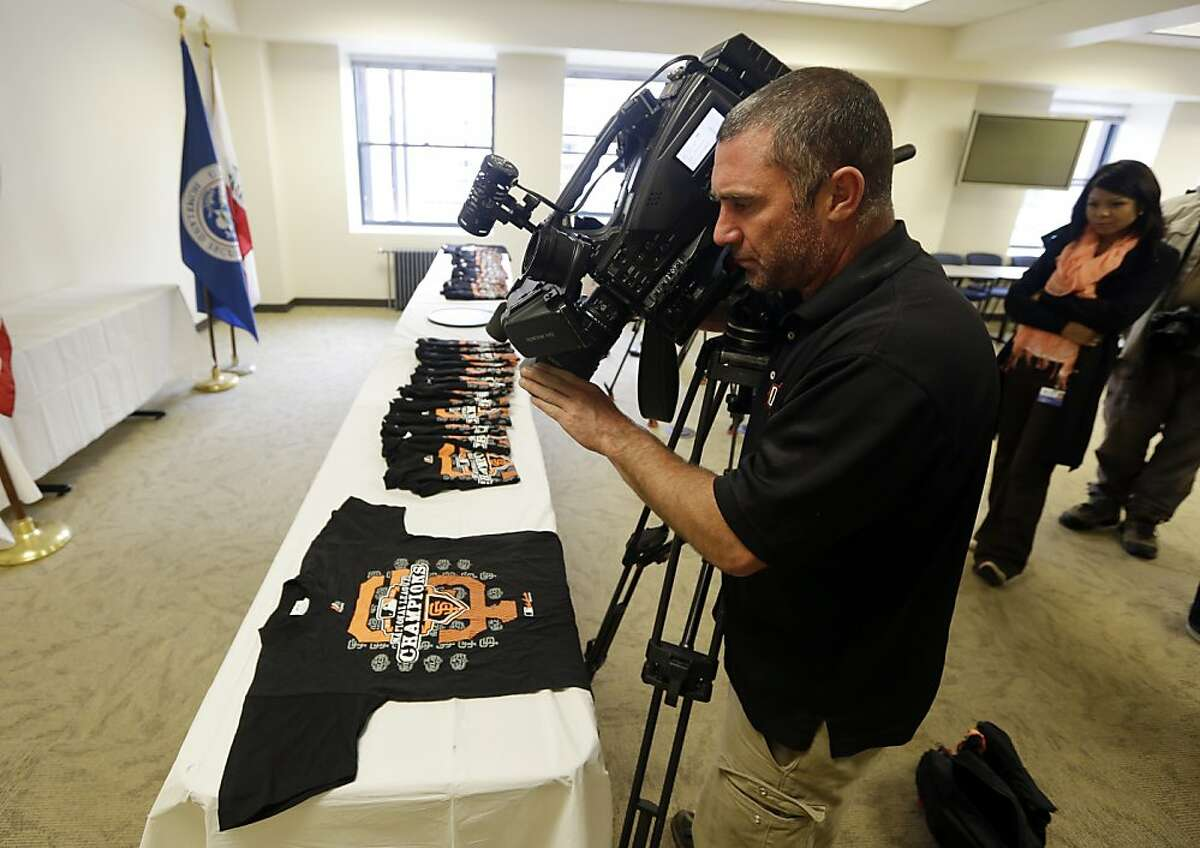 News photographer Gregg Welk shoots video of counterfeit San Francisco Giants T-shirts on display in San Francisco, Monday, Oct. 29, 2012. Agents with the U.S. Department of Homeland Security seized nearly 1,200 items of counterfeit MLB clothing being offered for sale by vendors on San Francisco streets. The merchandise included more than 1,000 phony T-shirts, along with counterfeit baseball hats and knit caps. The department estimated the value of the goods, if they were genuine, at $25,000. (AP Photo/Marcio Jose Sanchez)