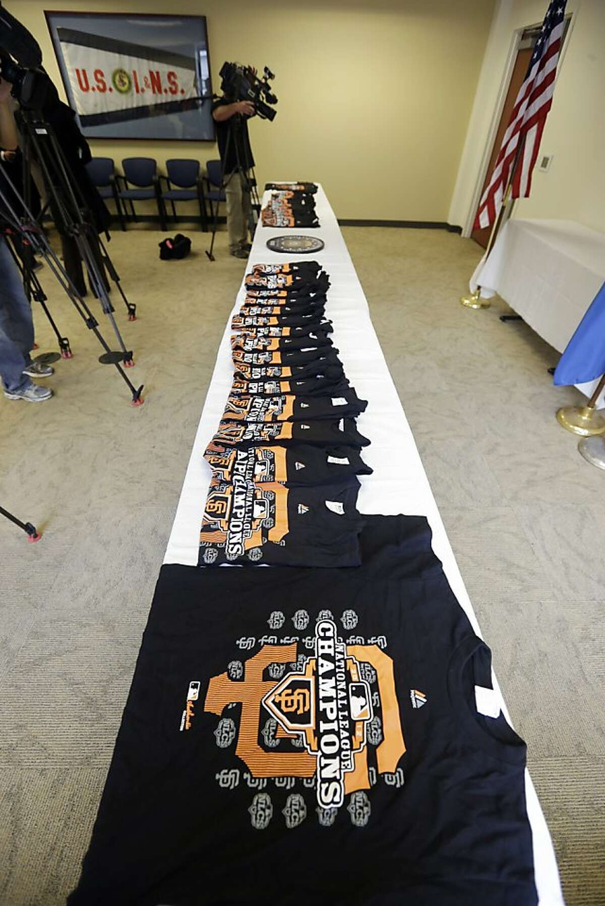 Counterfeit San Francisco Giants T-shirts are displayed in San Francisco, Monday, Oct. 29, 2012. Agents with the U.S. Department of Homeland Security seized nearly 1,200 items of counterfeit MLB clothing being offered for sale by vendors on San Francisco streets. The merchandise included more than 1,000 phony T-shirts, along with counterfeit baseball hats and knit caps. The department estimated the value of the goods, if they were genuine, at $25,000. (AP Photo/Marcio Jose Sanchez)