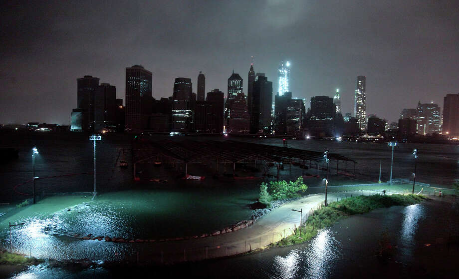 Lower Manhattan goes dark during hurricane Sandy, on Monday, Oct. 29, 2012, as seen from Brooklyn, N.Y. Sandy continued on its path Monday, as the storm forced the shutdown of mass transit, schools and financial markets, sending coastal residents fleeing, and threatening a dangerous mix of high winds and soaking rain.  Photo: Bebeto Matthews, AP / AP2012