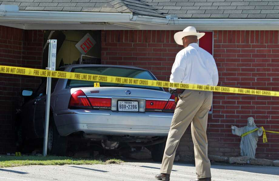 An investigator looks over a car that was crashed into the Greater Sweethome Missionary Baptist Church in Forest Hill, Texas, Monday, Oct. 29, 2012. Forest Hill Police Chief Dan Dennis says the pastor of the church is dead after the driver of the car crashed into the building and began to assault him. Dennis said officers arrived Monday afternoon at the Greater Sweethome Missionary Baptist Church to find an assault in progress. Dennis says the suspected attacker also later died shortly after being detained.   (AP Photo/LM Otero) Photo: LM Otero, Associated Press / AP