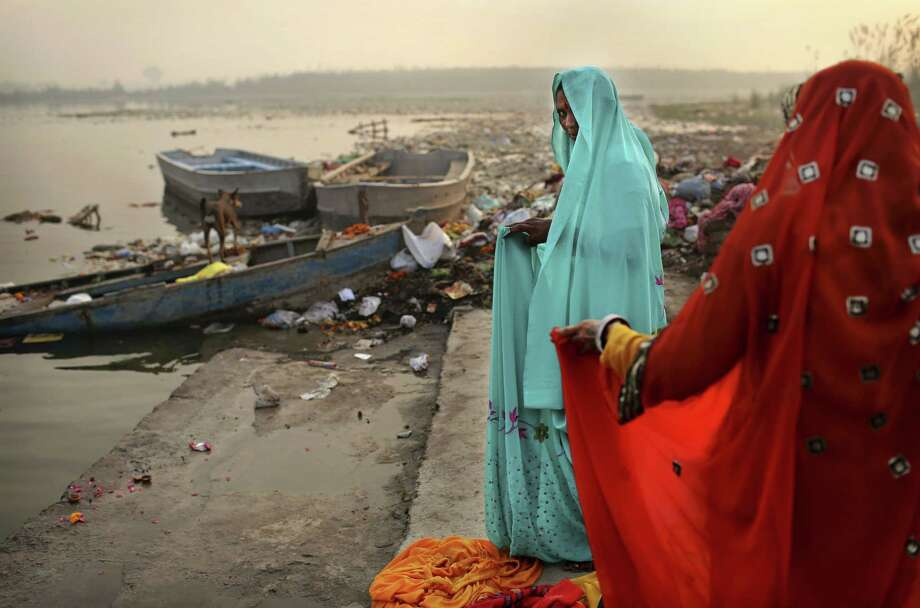 Indian female Hindu devotees put on saris after taking a holy dip in the Yamuna River on Sharad Purnima, an auspicious day for the new moon in the fall, in New Delhi, India, Monday, Oct. 29, 2012. (AP Photo/Kevin Frayer) Photo: Kevin Frayer, Associated Press / AP