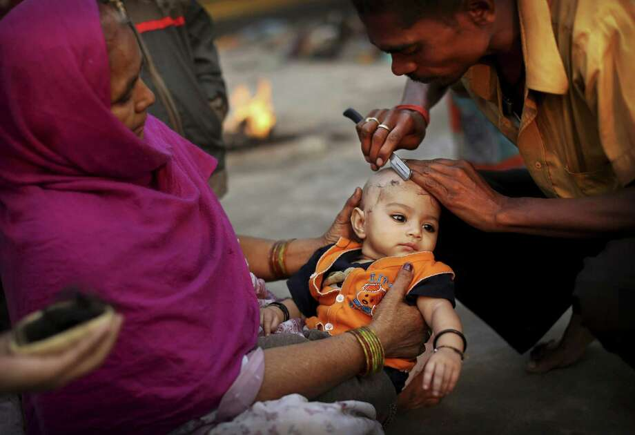 A barber gives an Indian Hindu boy his first haircut before going for a holy dip in the Yamuna River on Sharad Purnima, an auspicious day for the new moon in the fall, in New Delhi, India, Monday, Oct. 29, 2012. (AP Photo/KevinFrayer) Photo: Kevin Frayer, Associated Press / AP