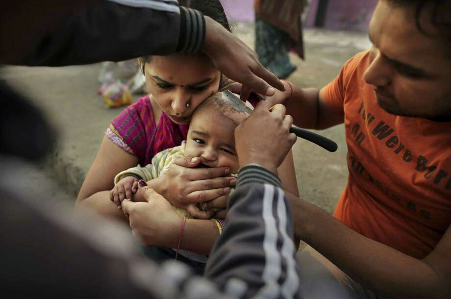 A barber gives Indian Hindu boy Vanshu, 5 months, his first haircut as he is held by his mother Rakhi Bansal, left, and father Amit before a holy dip in the Yamuna River on Sharad Purnima, an auspicious day for the new moon in the fall, in New Delhi, India, Monday, Oct. 29, 2012. (AP Photo/KevinFrayer) Photo: Kevin Frayer, Associated Press / AP