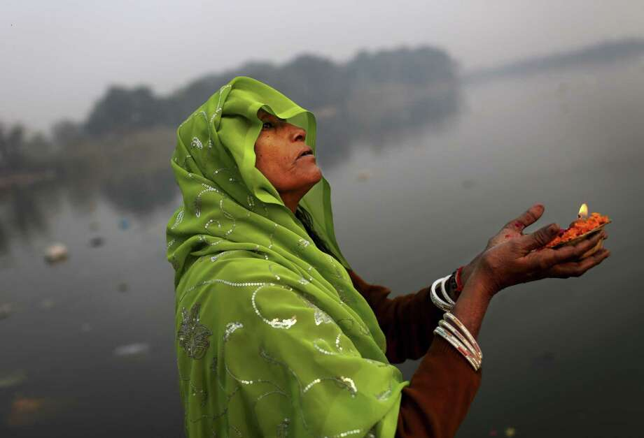 An Indian Hindu devotee performs a ritual on the Yamuna River on Sharad Purnima, an auspicious day for the new moon in the fall, in New Delhi, India, Monday, Oct. 29, 2012. (AP Photo/KevinFrayer) Photo: Kevin Frayer, Associated Press / AP