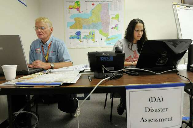 Red Cross workers, Chuck Allen, left, and Michelle McSweeney work on computers at the disaster operations center for the Red Cross Northeastern New York Chapter on Sunday, Oct. 28, 2012 in Colonie, NY.  Through the center the Red Cross coordinates with local and state agencies along with arranging for shelters and getting the supplies like food and water for the shelters along with who will be working in the shelters to assist residents coming in.   (Paul Buckowski / Times Union) Photo: Paul Buckowski