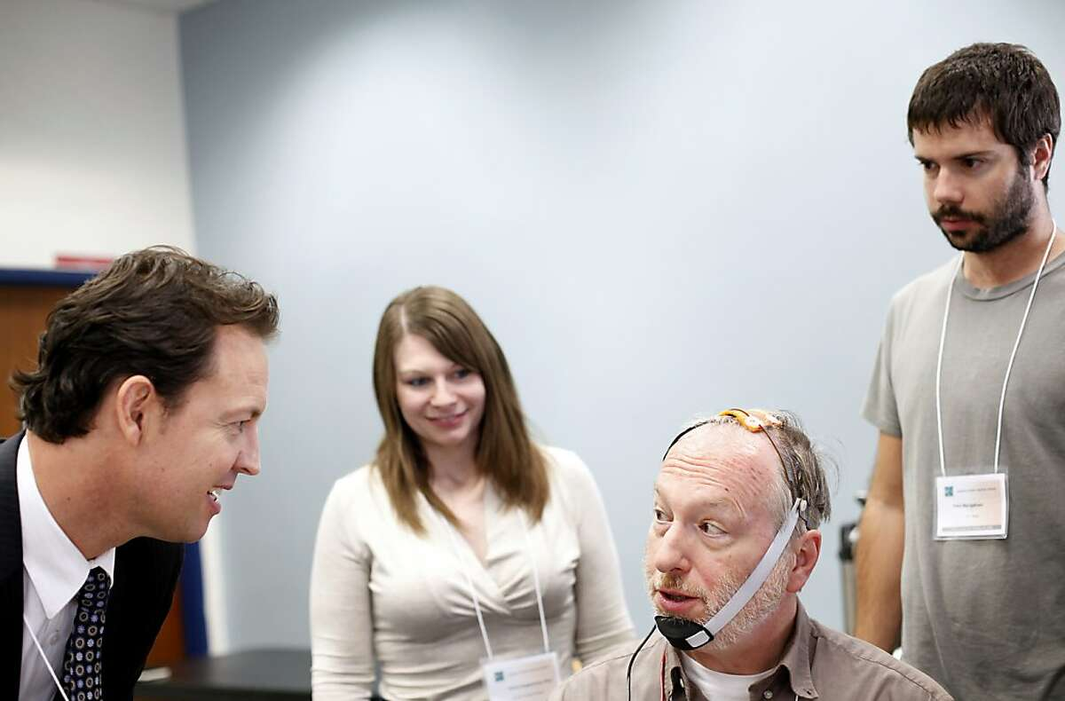 Dr. Dylan Edwards, left, checks in on Dr. Joel Younger during a demonstration of transcranial direct current stimulation at Highland Hospital in Oakland, Calif., Saturday, October 20, 2012. The procedure involves the delivery of a small current to the brain in a targeted area, and has the potential to aid in the treatment of lost motor skills after stroke or brain injury.