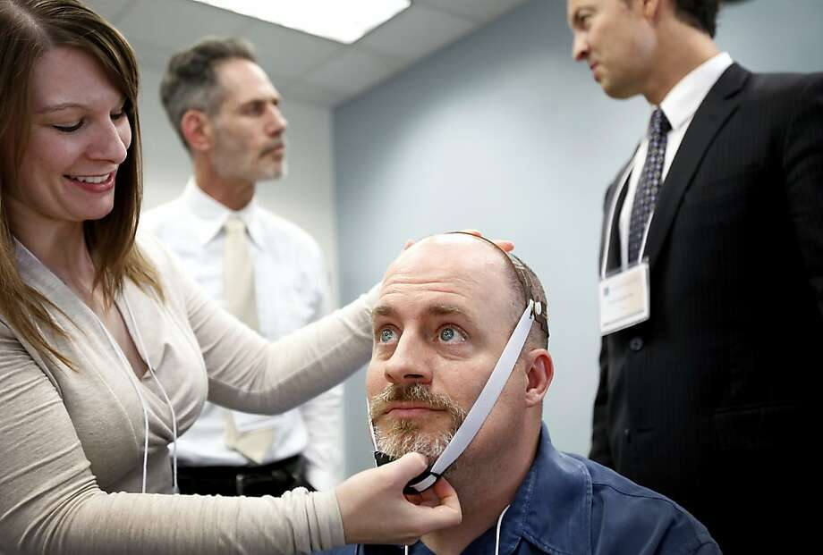 Dr. Emily Kappenman (left) prepares psychologist Michael Callaghan for transcranial direct current stimulation. Photo: Sarah Rice, Special To The Chronicle