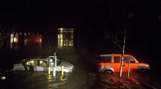 NEW YORK, NY - OCTOBER 29:  Flooded cars, caused by Hurricane Sandy, are seen on October 29, 2012, in the Financial District of New York, United States. Hurricane Sandy, which threatens 50 million people in the eastern third of the U.S., is expected to bring days of rain, high winds and possibly heavy snow. New York Governor Andrew Cuomo announced the closure of all New York City will bus, subway and commuter rail service as of Sunday evening Photo: Andrew Burton, Getty Images / 2012 Getty Images