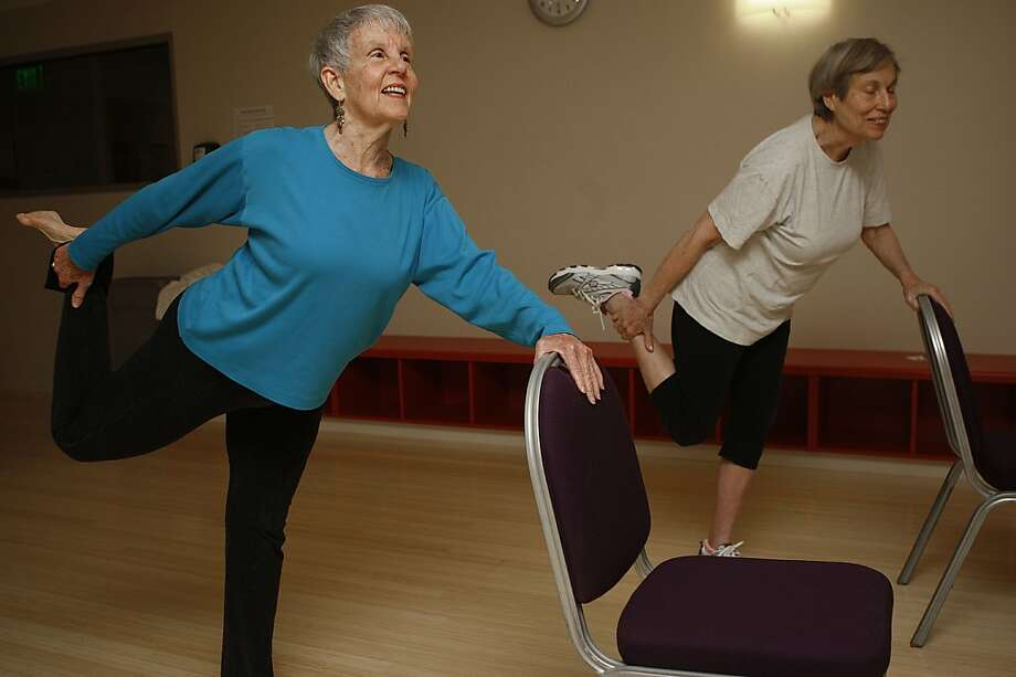 Yoga instructor Lily Anne Hillis (left) leads Evelyn Katchman, 80, in a stretching exercise at Moldaw Residences in Palo Alto. Photo: Liz Hafalia, The Chronicle