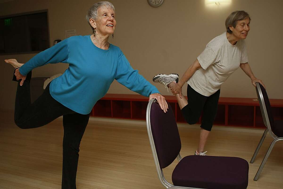Yoga teacher Lily Anne Hillis (left) doing a leg stretch with Evelyn Katchman, 80 years old, at Moldaw Residences in Palo Alto, Calif., on Monday, October 22, 2012.