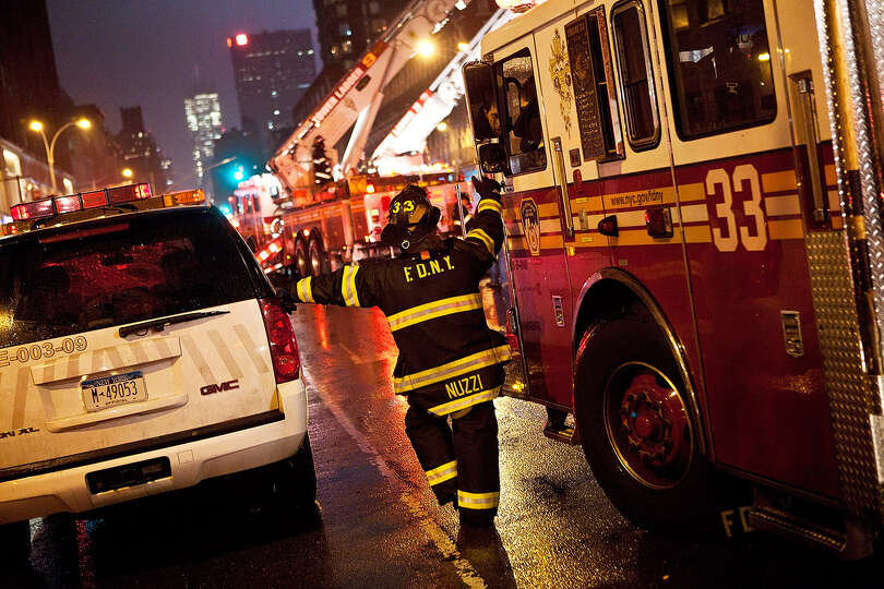 A fire fighter speaks to a colleague while cleaning up damage caused by Hurricane Sandy on October 2