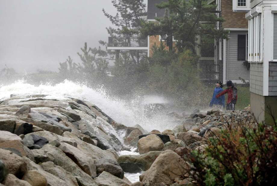 Viewers react as waves crash against a seawall near homes in Scituate, Mass. Monday, Oct. 29, 2012. Hurricane Sandy continued on its path Monday, as the storm forced the shutdown of mass transit, schools and financial markets, sending coastal residents fleeing, and threatening a dangerous mix of high winds and soaking rain. (AP Photo/Elise Amendola) Photo: Elise Amendola, STF / AP
