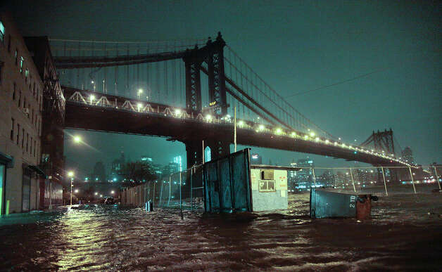 Streets are flooded under the Manhattan Bridge in the Dumbo section of Brooklyn, N.Y., Monday, Oct. 29, 2012. Sandy continued on its path Monday, as the storm forced the shutdown of mass transit, schools and financial markets, sending coastal residents fleeing, and threatening a dangerous mix of high winds and soaking rain. Photo: Bebeto Matthews, AP / AP2012
