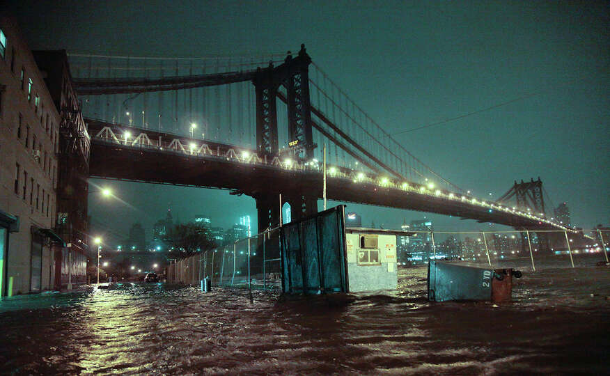 Streets are flooded under the Manhattan Bridge in the Dumbo section of Brooklyn, N.Y., Monday, Oct.