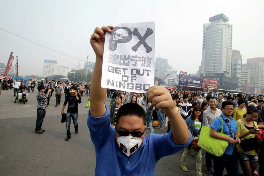 A protester holds up a banner in Zhejiang province's Ningbo city, protesting the proposed expansion of a polluting petrochemical factory. Photo: Ng Han Guan, STF / AP
