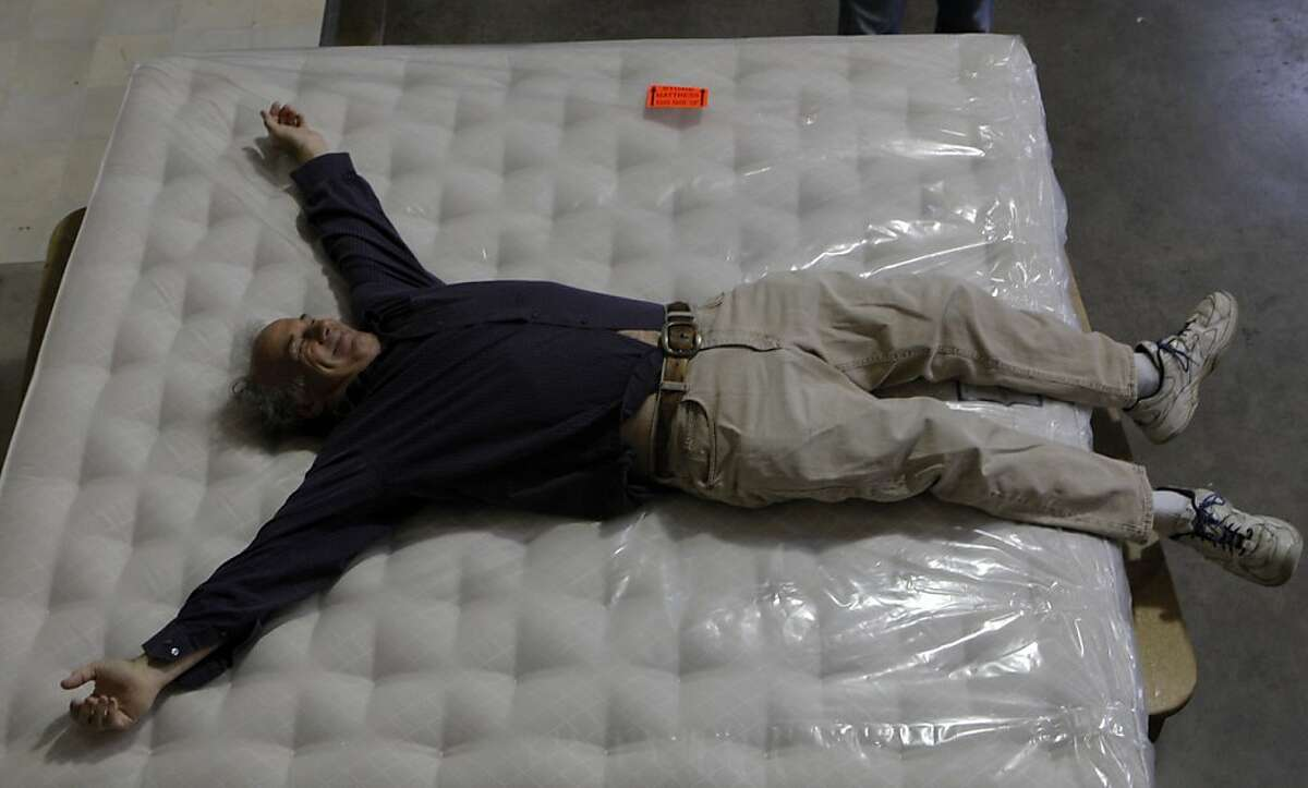 Reporter Steve Rubenstein smiles as he lays down to test a just finished mattress at McRoskey Mattress warehouse in San Francisco, Calif. on May 15, 2012.