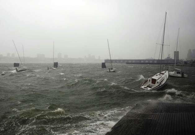 Sailboats rock in choppy water at a dock along the Hudson River Greenway during a storm, Monday, Oct. 29, 2012, in New York. Hurricane Sandy continued on its path Monday, forcing the shutdown of mass transit, schools and financial markets, sending coastal residents fleeing for higher ground, and threatening a dangerous mix of high winds and soaking rain. (AP Photo/Jeffrey Furticella) Photo: Jeffrey Furticella