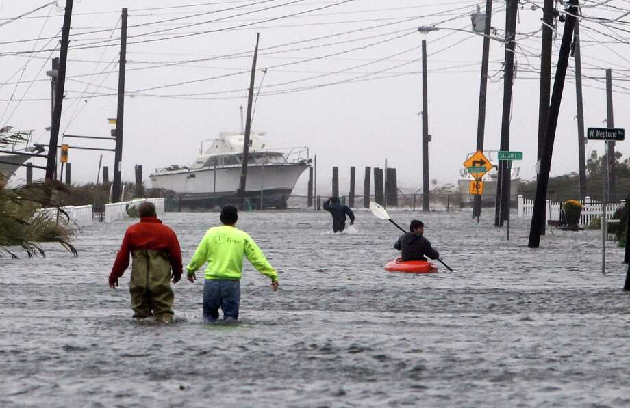 In the relative calm before the storm, people wade and paddle down a flooded street in Lindenhurst, N.Y., as Hurricane Sandy approached the East Coast on Monday Gaining speed and power through the day, the storm knocked out electricity to millions in the region. Photo: Jason DeCrow, FRE / FR103966 AP