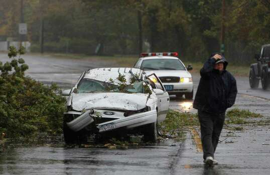 A car crushed by a fallen tree sits along Montauk Highway as Hurricane Sandy approaches, Monday, Oct. 29, 2012, in Bay Shore, N.Y.  Hurricane Sandy continued on its path Monday, forcing the shutdown of mass transit, schools and financial markets, sending coastal residents fleeing, and threatening a dangerous mix of high winds and soaking rain. (AP Photo/Jason DeCrow) Photo: Jason DeCrow, FRE / FR103966 AP