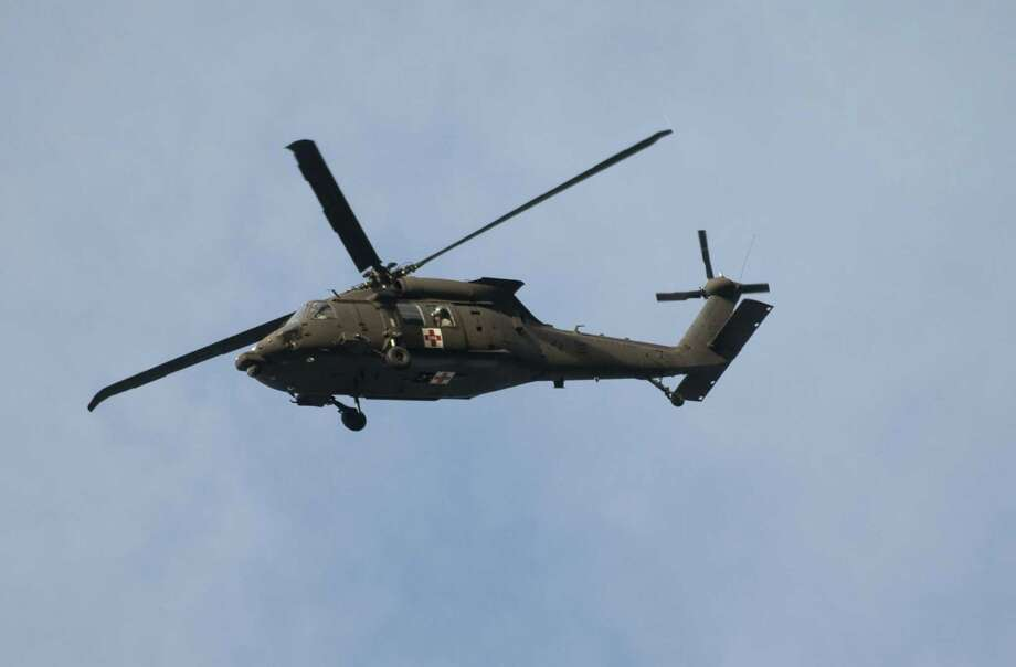 A National Guard helicopter soars over the command post on its way to search for two teenagers who failed to return from a day hike and were missing after two nights of wet, windy weather, Monday, Oct. 29, 2012. Deputy Nate Thompson of the Clackamas County sheriff's office said the two are Boy Scouts experienced in the outdoors, but authorities don't know what kind of gear they took with them. (AP Photo/The Oregonian, Brent Wojahn)  MAGS OUT; TV OUT; LOCAL TV OUT; LOCAL INTERNET OUT; THE MERCURY OUT; WILLAMETTE WEEK OUT; PAMPLIN MEDIA GROUP OUT Photo: Brent Wojahn, MBO / The Oregonian