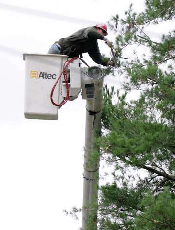 A worker from Lewis Tree Service trims trees around power lines Monday, Oct. 29, 2012 in Delmar, N.Y. Tree service companies were out all day trying to trim as many trees near power lines in anticipation of Hurricane Sandy's high winds. (Lori Van Buren / Times Union) Photo: Lori Van Buren