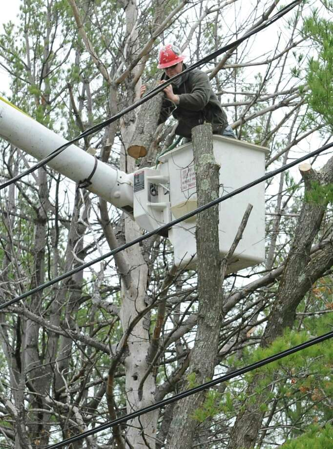 A worker from Lewis Tree Service throws down a piece of wood he just sawed off around power lines Monday, Oct. 29, 2012 in Delmar, N.Y. Tree service companies were out all day trying to trim as many trees near power lines in anticipation of Hurricane Sandy's high winds. (Lori Van Buren / Times Union) Photo: Lori Van Buren