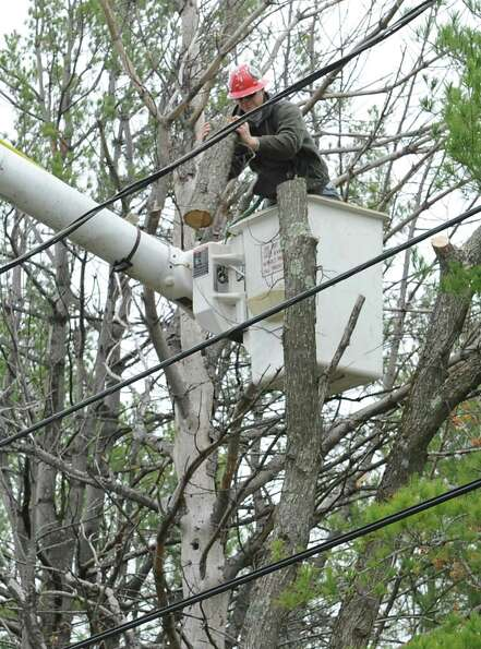 A worker from Lewis Tree Service throws down a piece of wood he just sawed off around power lines Mo
