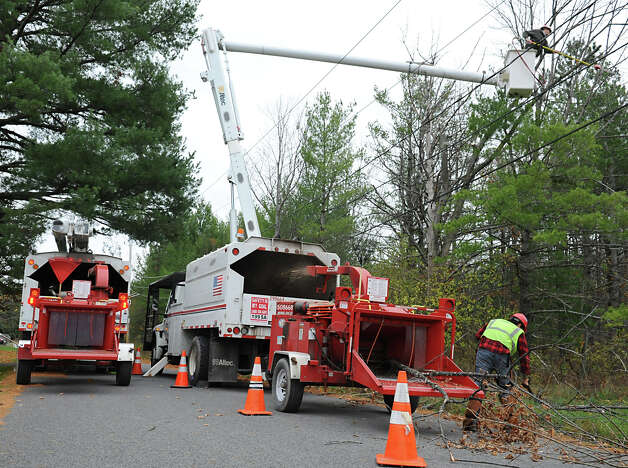 Workers from Lewis Tree Service trim trees around power lines Monday, Oct. 29, 2012 in Delmar, N.Y. Tree service companies were out all day trying to trim as many trees near power lines in anticipation of Hurricane Sandy's high winds. (Lori Van Buren / Times Union) Photo: Lori Van Buren