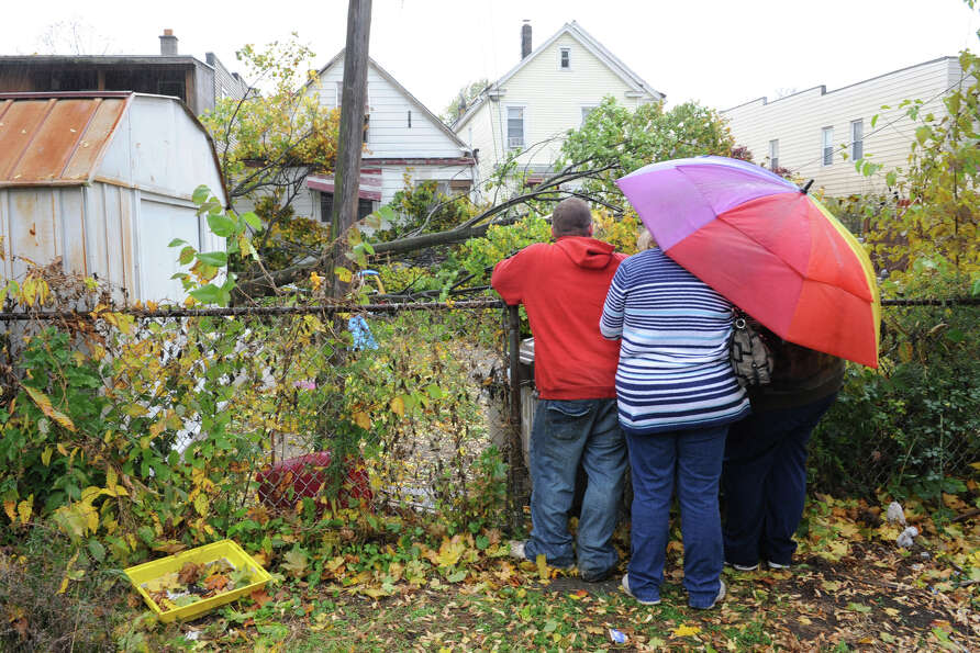 A family looks at the back of their house where a tree fell on it caused by Hurricane Sandy's high w
