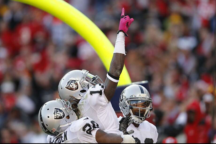 Denarius Moore (17) is lifted by Darren McFadden (20) and Rod Streater after his TD catch. Photo: Ed Zurga, Associated Press