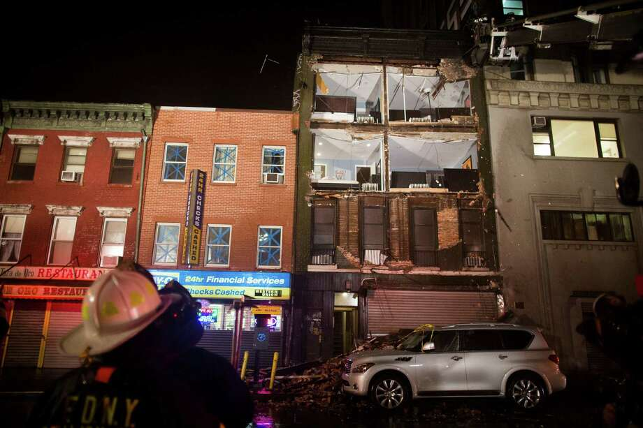 Firefighters look up at the facade of a four-story building on 14th Street and 8th Avenue that collapsed onto the sidewalk Monday, Oct. 29, 2012, in New York. Hurricane Sandy bore down on the Eastern Seaboard's largest cities Monday, forcing the shutdown of mass transit, schools and financial markets, sending coastal residents fleeing, and threatening a dangerous mix of high winds, soaking rain and a surging wall of water up to 11 feet tall. Photo: AP