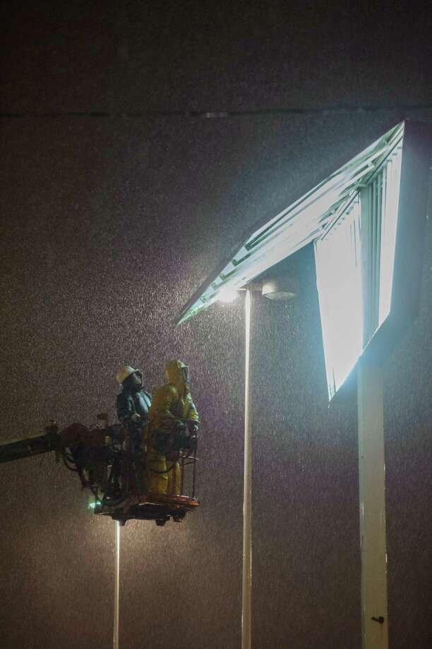 Repair crews works to repair a sign in inclement weather after strong storm winds caused a piece of a sign to fall, killing a woman, in Toronto on Monday, Oct. 29, 2012. Police said a woman had been killed by a falling sign while walking through a parking lot. Photo: AP