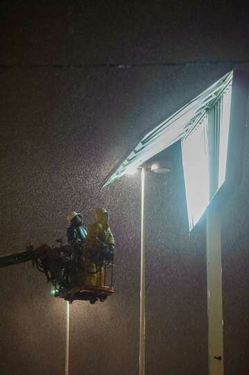 Repair crews works to repair a sign in inclement weather after strong storm winds caused a piece of