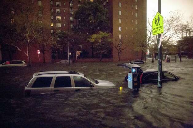 Vehicles are submerged on 14th Street near the Consolidated Edison power plant, Monday, Oct. 29, 2012, in New York. Sandy continued on its path Monday, as the storm forced the shutdown of mass transit, schools and financial markets, sending coastal residents fleeing, and threatening a dangerous mix of high winds and soaking rain.  Photo: AP