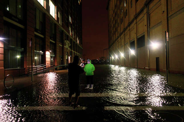 People take photographs in flood water in the Meatpacking District on October 29, 2012 in Manhattan, New York. Hurricane Sandy, which threatens 50 million people in the Mid-Atlantic area of the United States, is expected to bring days of rain, high winds and possibly heavy snow. New York Governor Andrew Cuomo announced the closure of all New York City bus, subway and commuter rail services as of Sunday evening. Photo: Allison Joyce, Getty Images / 2012 Getty Images