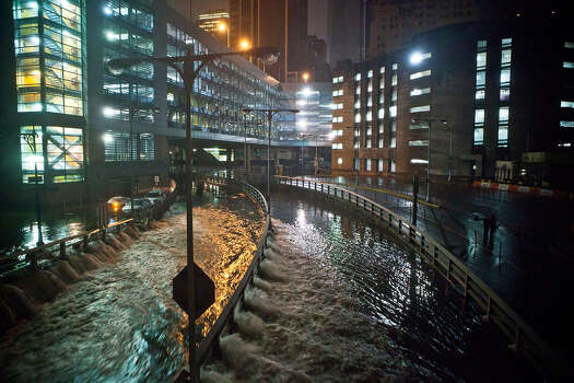 Water rushes into the Carey Tunnel (previously the Brooklyn Battery Tunnel), caused by Hurricane Sandy, October 29, 2012, in the Financial District of New York, United States. Hurricane Sandy, which threatens 50 million people in the eastern third of the U.S., is expected to bring days of rain, high winds and possibly heavy snow. New York Governor Andrew Cuomo announced the closure of all New York City will bus, subway and commuter rail service as of Sunday evening Photo: Andrew Burton, Getty Images / 2012 Getty Images