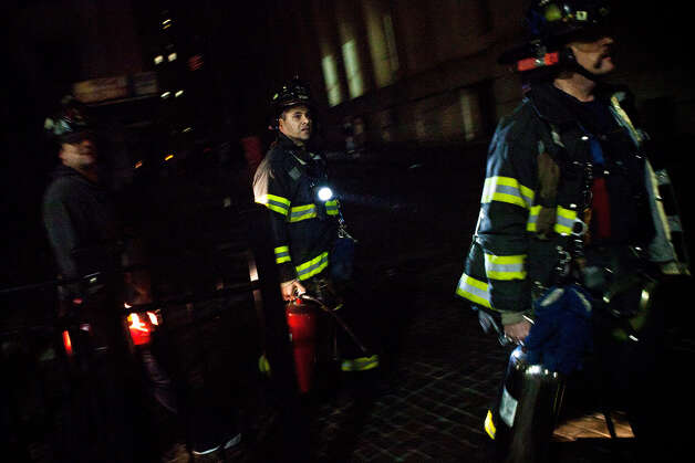 Fire fighters walk down the street during the landfall of Hurricane Sandy, on October 29, 2012, in the Financial District of New York, United States. Hurricane Sandy, which threatens 50 million people in the eastern third of the U.S., is expected to bring days of rain, high winds and possibly heavy snow. New York Governor Andrew Cuomo announced the closure of all New York City will bus, subway and commuter rail service as of Sunday evening Photo: Andrew Burton, Getty Images / 2012 Getty Images