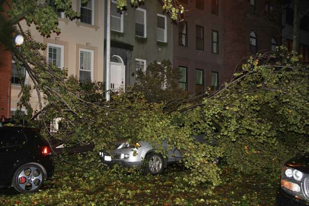 A fallen tree branch sits on a car blocking East 74th St. between Lexington Avenue and Third Avenue on Manhattan's Upper West Side on Monday, Oct. 29, 2012. Sandy made landfall Monday night, hurling a surge of seawater on New York City with wind and rain that sent water sloshing into Manhattan from three sides but began dying down within hours. (AP Photo/Willie Regan) Photo: Willie Regan