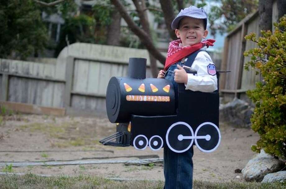 """FINALIST! I love how Jacob sells this costume with a huge smile. From parents Josh and Darlene: """"We made the train from an old diaper box, cardboard tube, and black paint. We got the hat and patches at a train museum. He's really looking forward to taking a run on the Candy Express!"""" (Jacob was a winner in 2010 for his """"E.T."""" costume.)"""