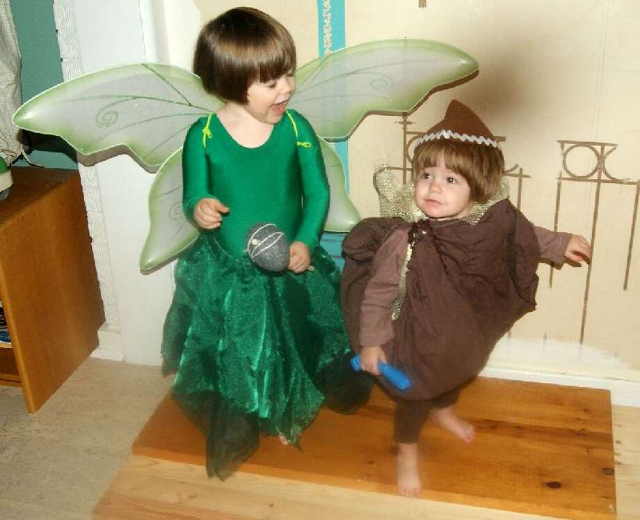 "FINALIST! Longtime The Poop reader Jody H. returns with fairy and bag-of-pixie dust costumes for her girls Eliza and Gillian. (""If we're lucky on Halloween night, I might be able to get some glitter on Gillian before she rips off the entire costume."") Bonus points to Jody for re-purposing Eliza's old Bilbo Baggins hat -- she was a 2010 winner -- for Gillian's ensemble."