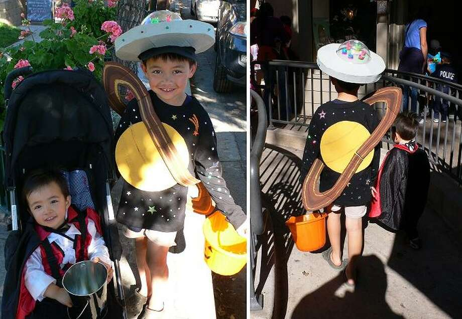 "FINALIST! Eric S. made this excellent planet Saturn costume for his son. ""Realizing something was missing, I made a flying saucer hat out of more cardboard,  attached blinking lights on the rim (a Christmas light LED necklace),  and added a crew of aliens peering out of a plastic bowl saucer dome."""
