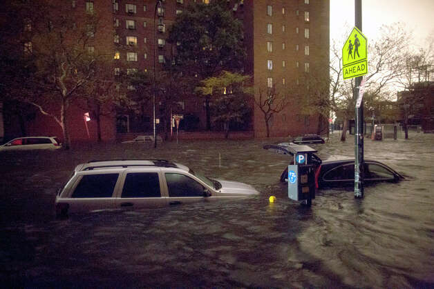 Vehicles are submerged on 14th Street near the Consolidated Edison power plant, Monday, Oct. 29, 2012, in New York. Sandy continued on its path Monday, as the storm forced the shutdown of mass transit, schools and financial markets, sending coastal residents fleeing, and threatening a dangerous mix of high winds and soaking rain. Photo: John Minchillo, AP / AP2012