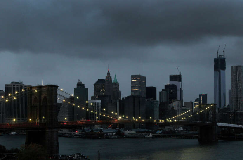 The lights on the Brooklyn Bridge stand in contrast to the lower Manhattan skyline which has lost it